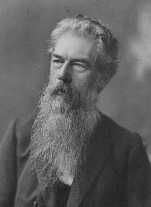 Bust-length black and white portrait of Selfe with long grey beard, looking into the distance.