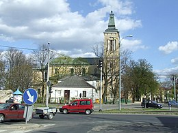 Colour picture of a road intersection, with a large neo-classical church in the background