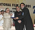 Pranab Mukherjee presenting the Swarna Kamal Award for the Best Popular Film for providing wholesome entertainment to the Director Rakeysh Omprakash Mehra for Bhaag Milkha Bhaag (Hindi).jpg