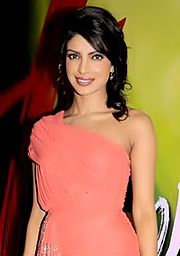 Priyanka Chopra in a light pink dress smiling towards the camera at a press event