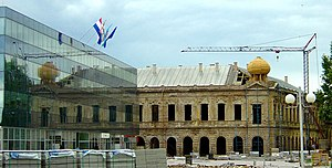 A large damaged building under restoration with a modern glass building visible in the foreground, flying various flags. A construction crane and building materials are also visible.