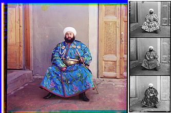 A large color photograph abutting (to its right) a column of three stacked black-and-white versions of the same picture. Each of the three smaller black-and-white photos are slightly different, due to the effect of the color filter used. Each of the four photographs differs only in color and depict a turbaned and bearded man, sitting in the corner an empty room, with an open door to his right and a closed door to his left. The man is wearing an ornate full-length blue robe trimmed with a checkered red-and-black ribbon. The blue fabric is festooned with depictions of stems of white, purple, and blue flowers. He wears an ornate gold belt, and in his left hand, he holds a gold sword and scabbard. Under his right shoulder strap is a white aiguillette; attached to his robe across his upper chest are four multi-pointed badges of various shapes, perhaps military or royal decorations.