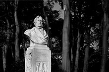 A white bust on a square stand that bears Wagner's name. There are trees behind it.