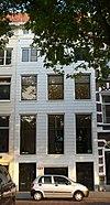 Koopmanshuis, met gepleisterde lijstgevel. Onder de kroonlijst liggende vensters, gescheiden door triglyfen