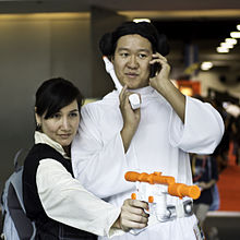 Photograph of two Star Wars cosplayers: A woman dressed as the male character Han Solo and a man dressed as the female character Princess Leia.