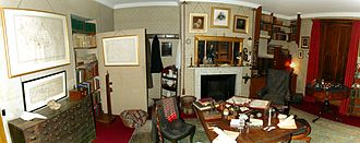 Down House - Charles Darwin's study at Down House, restored with original furniture including his wheeled armchair and writing board. On the right, two (shuttered) windows look east, and Darwin had an angled mirror fixed outside to see who was coming up the drive to the entrance.