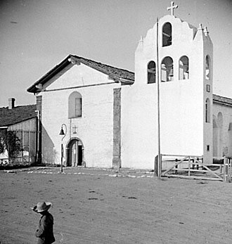 Mission Santa Inés - Mission Santa Inés in about 1912. The mission's original three-bell campanario, erected in 1817, collapsed in a storm in 1911 and was subsequently replaced by this concrete four-bell version, which also had openings on the side. This tower was replaced in 1948 to restore the original three-niched appearance. It has been compared by architectural historian Rexford Newcomb to the one that originally abutted the façade of Mission San Gabriel Arcángel.