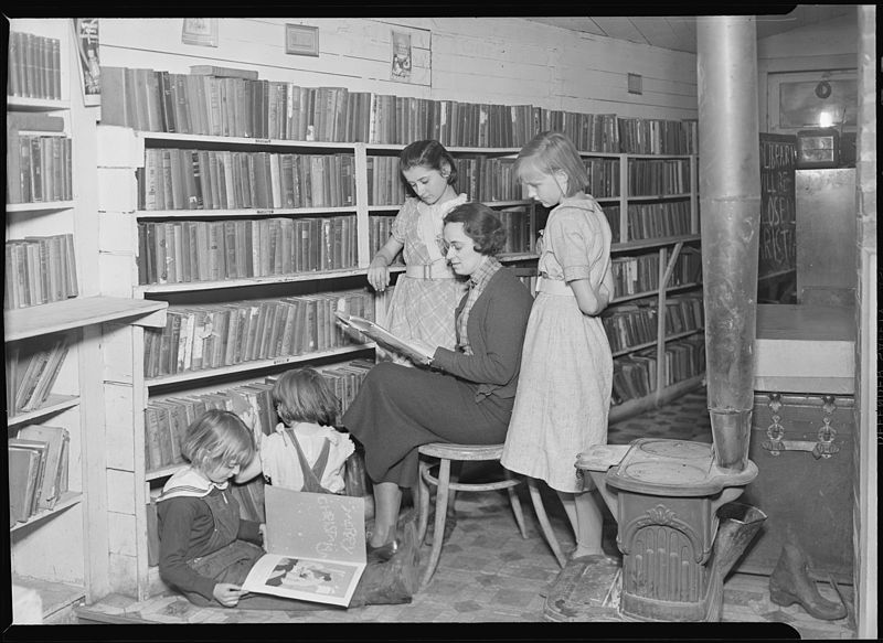 Woman reading with a group of children. Scott's Run, West Virginia (1937). Image in the public domain, made available by the National Archives and Records Administration.