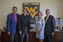 Three older men and one woman pose in front of a framed University of West Virginia logo.
