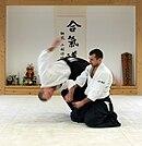 """Một phiên bản của động tác """"ném bốn hướng"""" (shihōnage) với người tấn công đang đứng và người phòng thủ ngồi."""