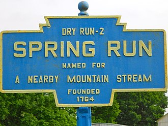 Keystone Markers - Keystone Marker for Spring Run, Pennsylvania, which includes all the standard elements of the markers: 1) a light blue and yellow color scheme, 2) distance to the next town, 3) town name and origin of the name, 4) founding date, and 5) a distinctive shape, cast in iron and mounted on a distinctive pole.
