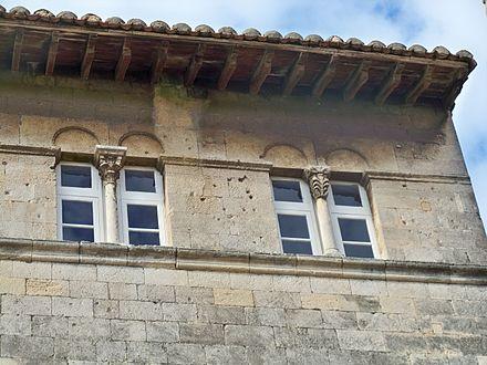 Fenêtre romane à linteau à profil courbe, à arc simulé délardé en bas-relief dans la tête du linteau et à cordon d'imposte.