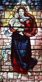 Mary is shown standing holding the baby Jesus high in her arms