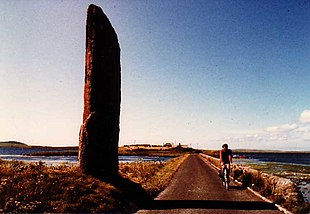 "The Stenness <em>Watch Stone</em> stands outside the circle, next to the modern bridge leading to the <a href=""http://search.lycos.com/web/?_z=0&q=%22Ring%20of%20Brodgar%22"">Ring of Brodgar</a>"
