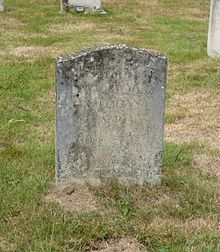 A granite headstone, discoloured by moss, in a grassy churchyard