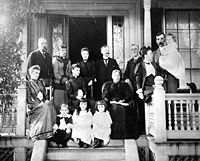 Late 19th century photo of a family of ten adults and four children posing on the front porch of a large house. The women wear long dresses with high collars and leg-o-mutton sleeves. The men have flowing moustaches. Marjory is a toddler in a long dress and black stockings.