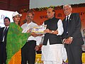 The Union Home Minister, Shri Rajnath Singh presenting the Account Opening Kit to beneficiaries of the 'Pradhan Mantri Jan Dhan Yojana (PMJDY)', in Lucknow on August 28, 2014.jpg