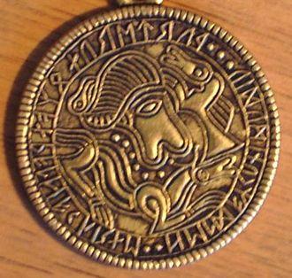 "Walhaz - Brass replica of the Tjurkö bracteate showing the word walhakurne (""Roman grain"", i.e. gold coin)"