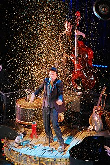 Tom waits discography wikipedia tom waits discography a man performing on stage surrounded by confetti several instruments surround him and stopboris Choice Image