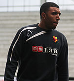 "A young man wearing a black and white top. The logo on his top is coloured red, black and yellow, and reads ""WATFORD"""