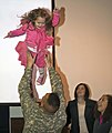 U.S. Army Sgt. Drew Kirts holds his his daughter high at the Camp Atterbury Joint Maneuver Training Center in central Indiana, Feb. 27, 2010.jpg