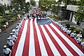 U.S. Coast Guardsmen assigned to units based in the Pacific Northwest and U.S. Coast Guard Auxiliary personnel carry an American flag through Seattle Center to the beginning of the Alaska Airlines Seafair 130727-G-ED165-956.jpg