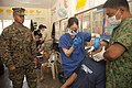 U.S. Marine Corps Brig. Gen. Craig Q. Timberlake, left, the commanding general of the 3rd Marine Expeditionary Brigade, watches a tooth extraction during a dental and medical civic action program at the Amungan 130407-M-UY788-116.jpg