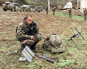 Multi-National Division (North) (Bosnia) - A US Army signaller assigned to Multi-National Division (North) using a satellite phone near the village of Skugric in 1999