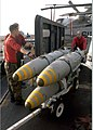 US Navy 030305-N-9234B-002 Aviation Ordnanceman 1st Class Michael Green pushes bombs off the weapons elevator.jpg