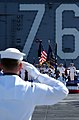 US Navy 040615-N-5549O-049 Senior leadership and Sailors aboard the aircraft carrier USS Ronald Reagan (CVN 76), salute the National Ensign during a remembrance memorial to former President Ronald Reagan.jpg
