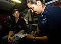 US Navy 041207-N-2984R-092 NASCAR Nextel Cup driver John Andretti is interviewed by Journalist 3rd Class Alma R. Larson in the Carrier Air Traffic Control Center (CATCC) aboard the Nimitz-class aircraft carrier USS Harry S. Tru.jpg