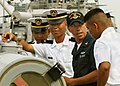 US Navy 050818-N-7415V-001 Torpedoman's Mate 3rd Class Kelly Trahan, assigned to the guided missile destroyer USS Paul Hamilton (DDG 60), explains the operation of the a surface vessel torpedo tube to a group of Philippine Navy.jpg