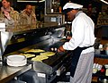 US Navy 070206-N-1831S-018 Culinary Specialist 3rd Class Eric Williams prepares eggs for the breakfast crowd.jpg