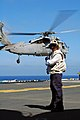 US Navy 070914-N-7643B-001 Aviation Boatswain's Mate (Handling) 1st Class Daniel Guevara awaits the landing of a MH-60S Seahawk, assigned to the Blackjacks of Helicopter Support Command Squadron (HSC) 21, aboard USS Tarawa (LHA.jpg