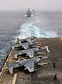 US Navy 070918-N-4774B-061 AV-8B Harriers line the flight deck of amphibious assault ship USS Tarawa (LHA 1) while dock landing ship USS Germantown (LSD 42) and other members of Tarawa battle group follow closely behind.jpg