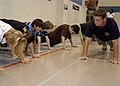 US Navy 071002-N-5208T-003 Students at Heritage Elementary receive instruction on proper push-up technique from members of Special Boat Unit, Team 12, from San Diego.jpg