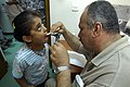 US Navy 080828-N-0292S-005 An Iraqi doctor checks a child's throat during an examination at a free health clinic during a combined medical event for local Iraqi families.jpg