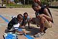 US Navy 090402-N-4143O-003 Storekeeper 2nd Class Eric Jones gets help painting a basketball court from neighborhood children during a Southern Partnership Station community relations project.jpg