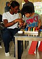 US Navy 100311-N-1200S-140 Information Systems Technician 3rd Class Erica Watkins teaches a young girl how to thread a necklace.jpg