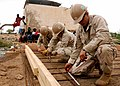 US Navy 100428-N-8936G-042 Builder Constructionman Joseph Scott, Builder Constructionman Selina Rodriguez and Equipment Operator Constructionman Apprentice Corey Moore measure and secure rebar framework on a water distribution.jpg
