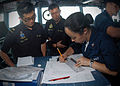 US Navy 100710-N-0995C-072 Operations Specialist 2nd Class Jessica Proudfoot plots courses on a maneuvering board with Republic of Singapore Navy officers on the bridge of the guided-missile destroyer USS Chung-Hoon (DDG 93).jpg