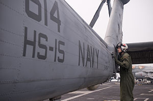 US Navy 111230-N-TZ605-399 Naval Air Crewman 2nd Class Sean Murphy, assigned to Helicopter Anti-Submarine Squadron (HS) 15, inspects an SH-60F Sea.jpg