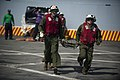 US Navy 120103-N-PB383-464 Marines assigned to the 11th Marine Expeditionary Unit (11th MEU) carry a stretcher during a flight deck firefighting ex.jpg