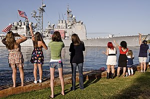 US Navy 120213-N-QG393-011 Friends and family members of Sailors assigned to the guided-missile cruiser USS Port Royal (CG 73) wave to the ship as.jpg