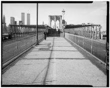 Ein Blick auf die Brooklyn Bridge im Jahr 1982, der die Stufen zeigt, die früher zur Fußgängerpromenade führten.  Im Hintergrund befindet sich ein Hängeturm