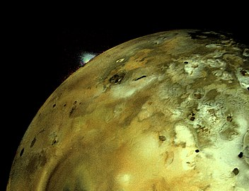 A volcanic eruption plume rises over the limb of Io