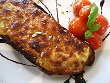 Photograph of a Welsh rarebit, melted cheese on toast
