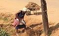 Woman Clearing Busy roadside in Mbarara.jpg