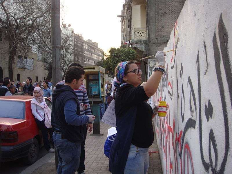 File:Women of Cairo painting revolutionary wall slogans.jpg