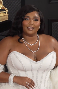 Lizzo smiles in a white dress